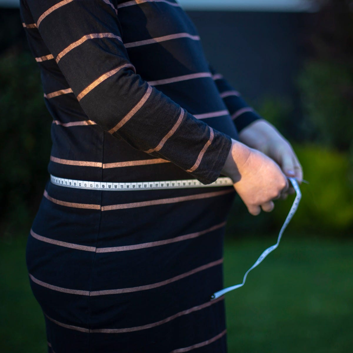 pregnant woman measuring tape belly
